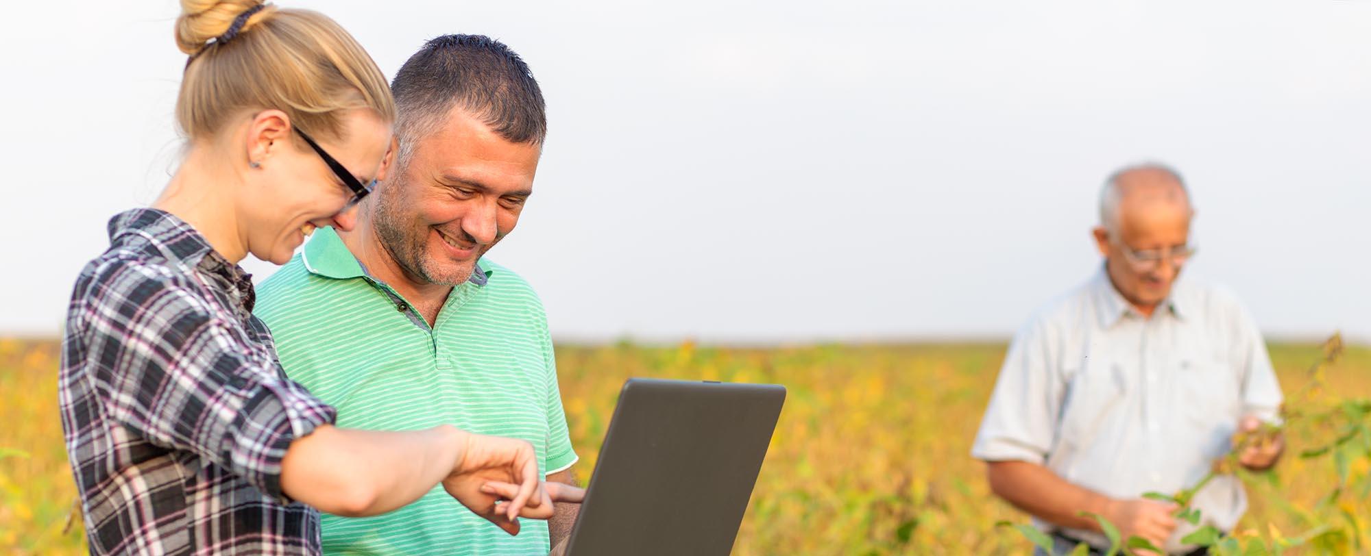 Farmers in field discuss Australian environmental markets